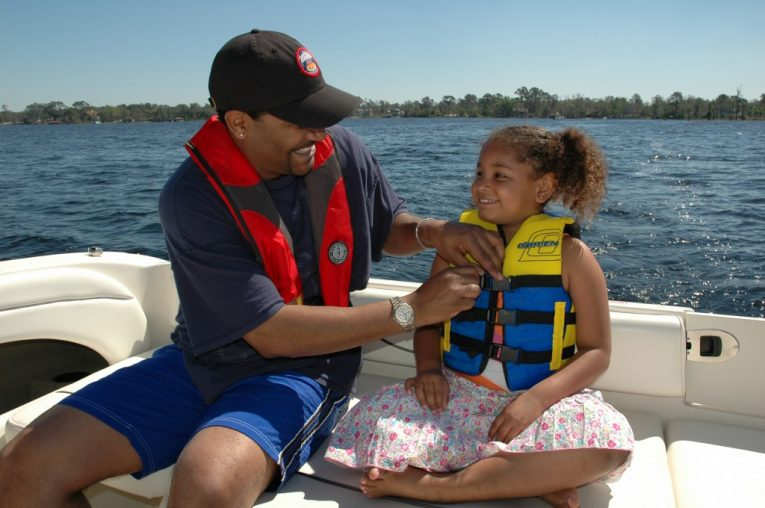 Father helping daughter inspect life jacket personal flotation device