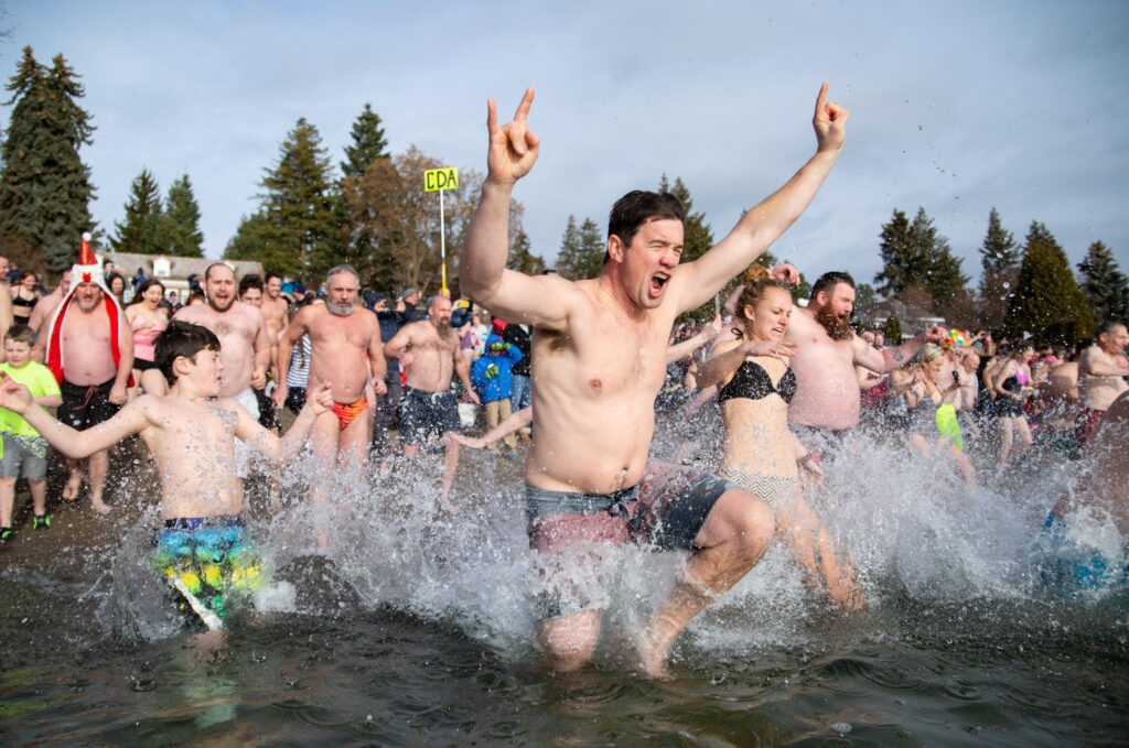 Man raising rock on symbols in air running into lake with large crowd behind him