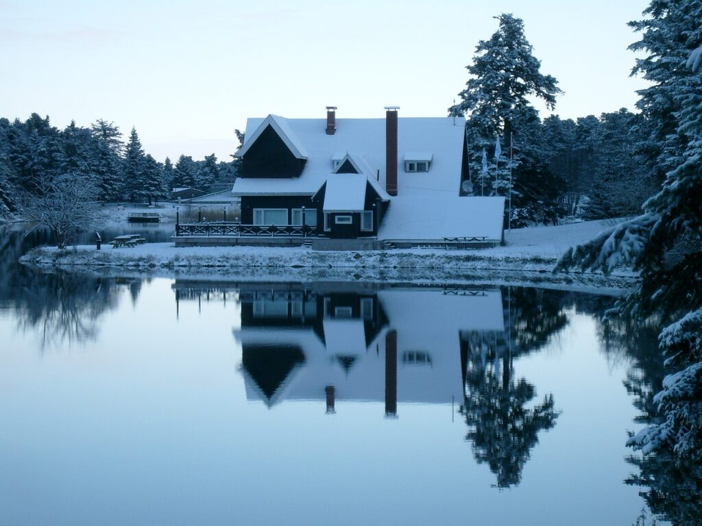 Lake house during winter with snow and still lake