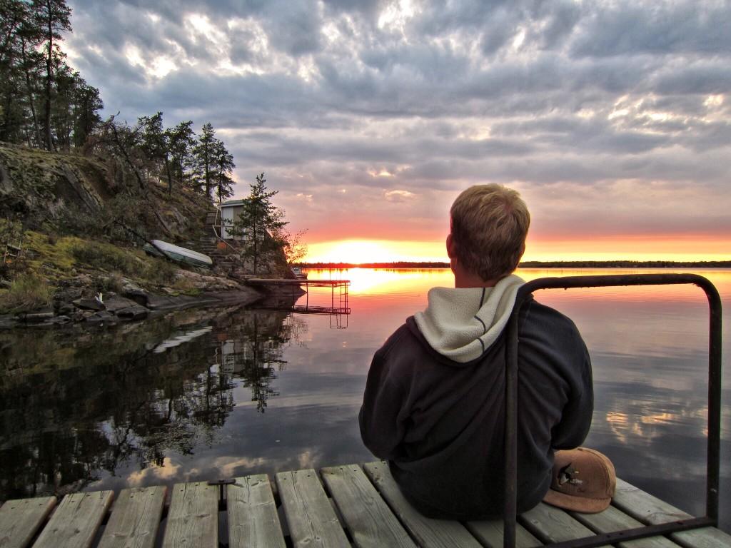 Man sitting on lake dock enjoying sunset