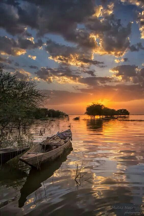 canoe on lake during sunset with clouds