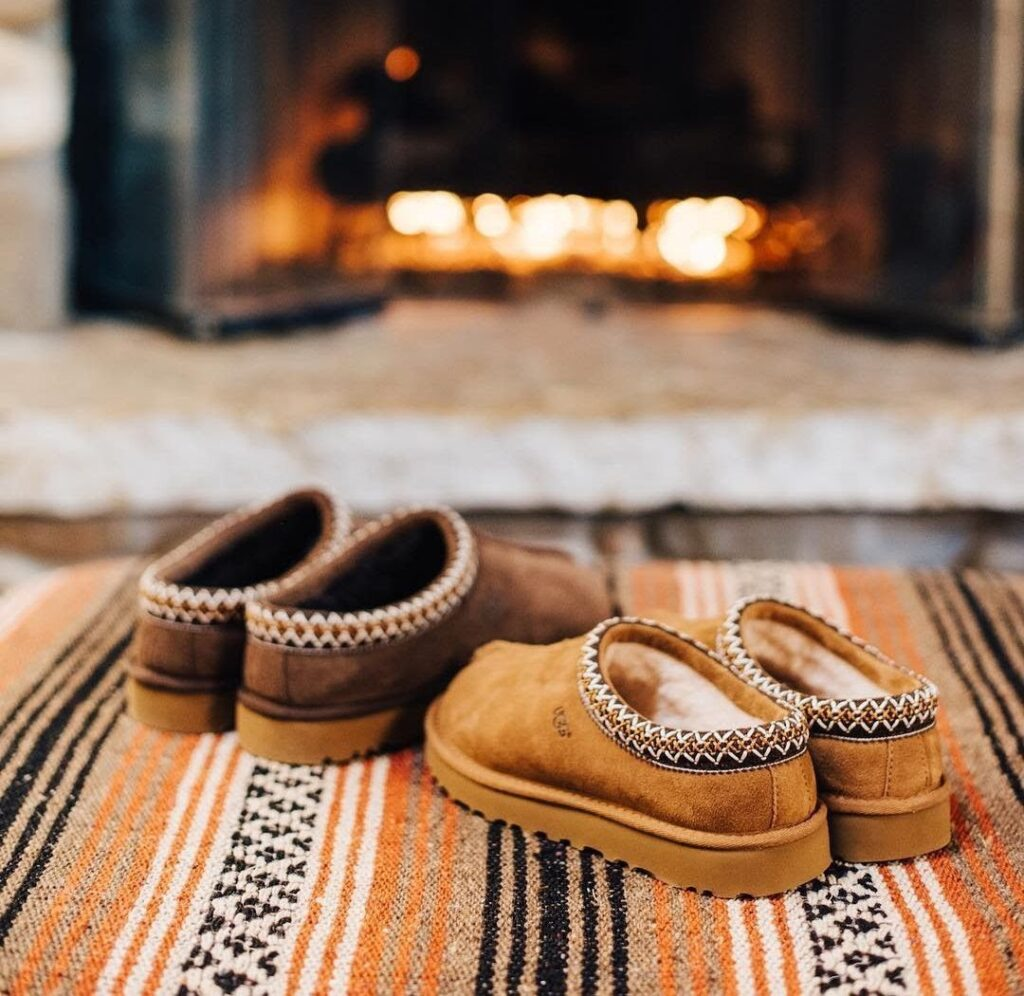 Cozy winter Ugg slippers in front of fireplace at lake house