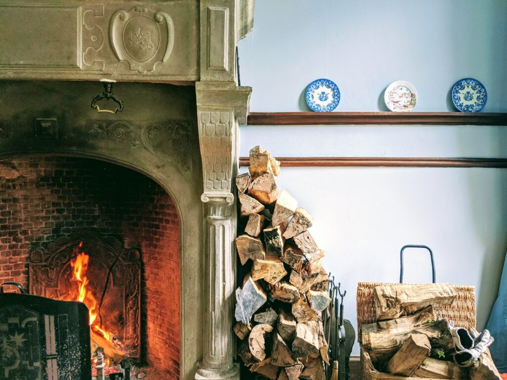 Pile of chopped firewood leaning  against lit wood fireplace