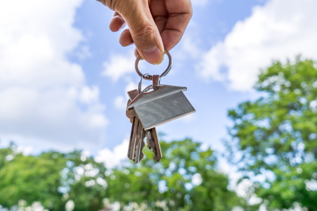 Person holding set of keys with house keychain in the air