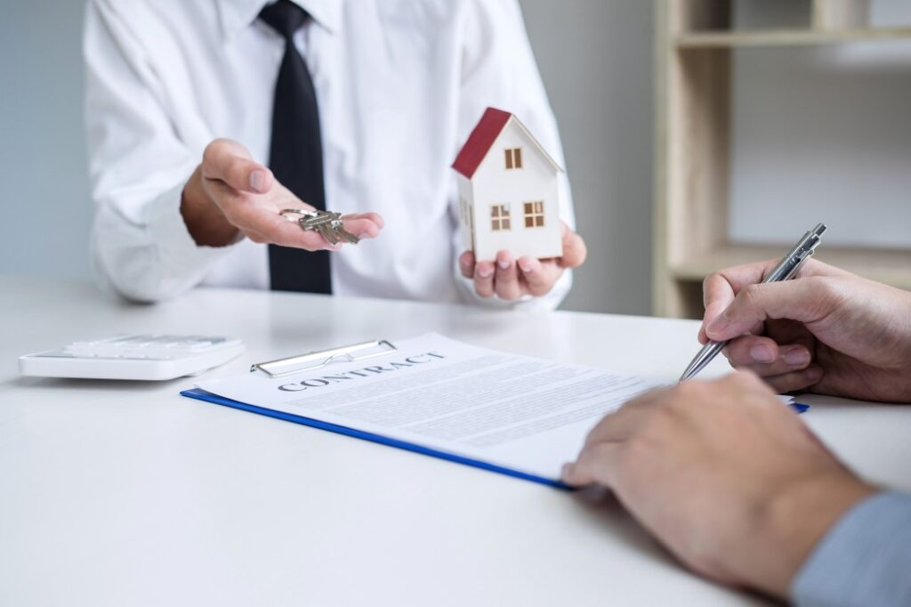 Person holding house and keys in hand while homebuyer signs leased land contract