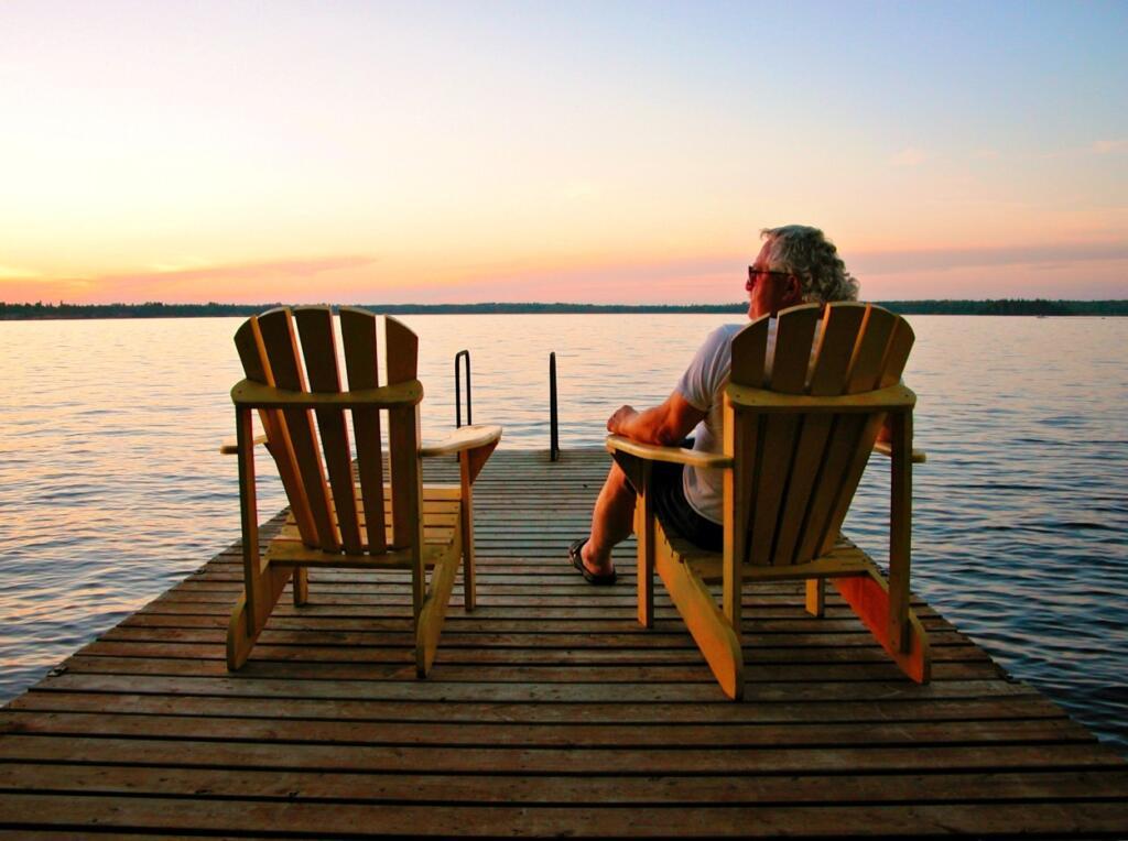 Older retired man relaxing on dock at lake