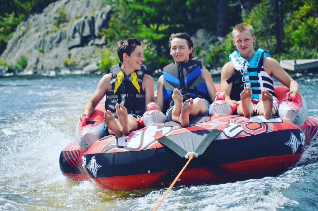 three boys sitting on raft at lake
