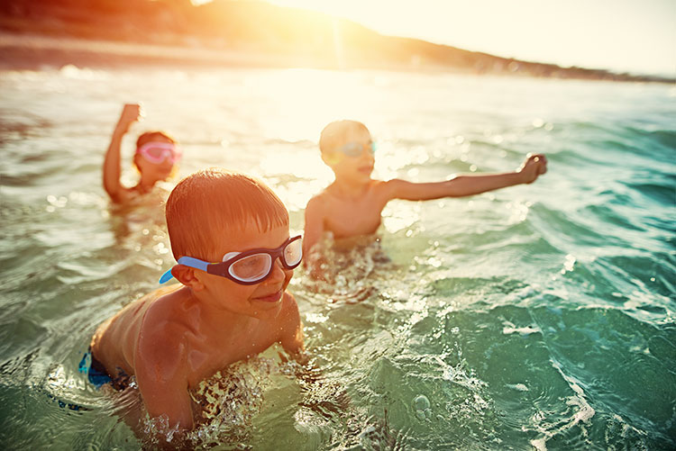 Happy children playing in water at beach