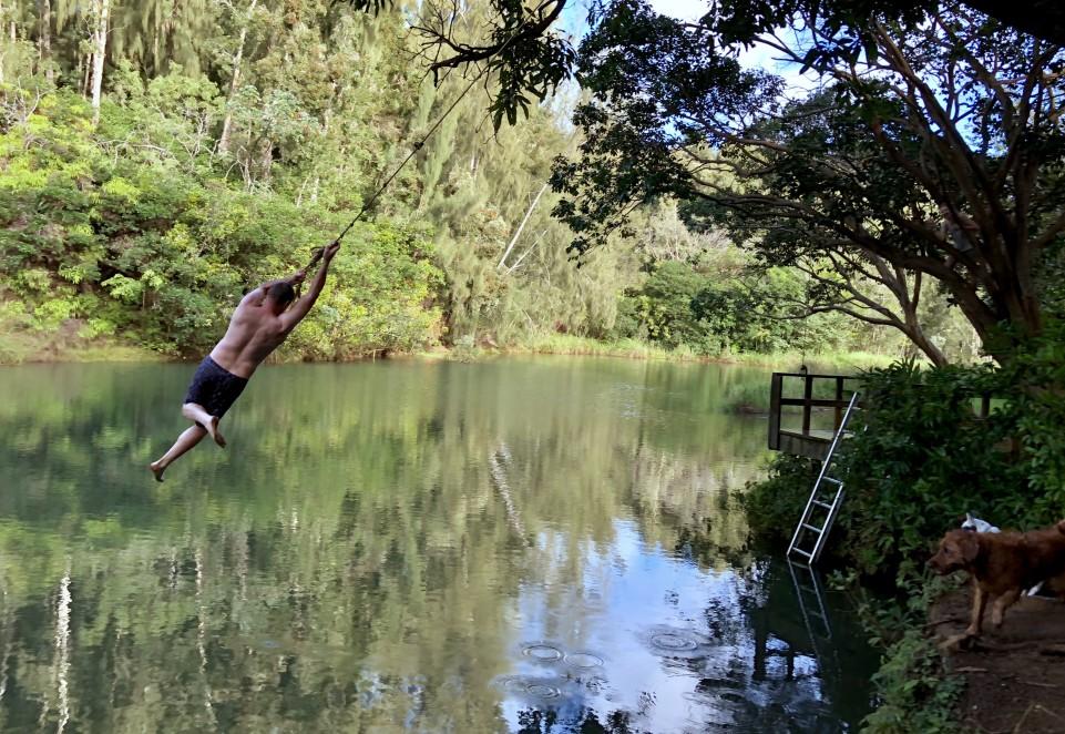 Man swinging on rope swing at lake with dog