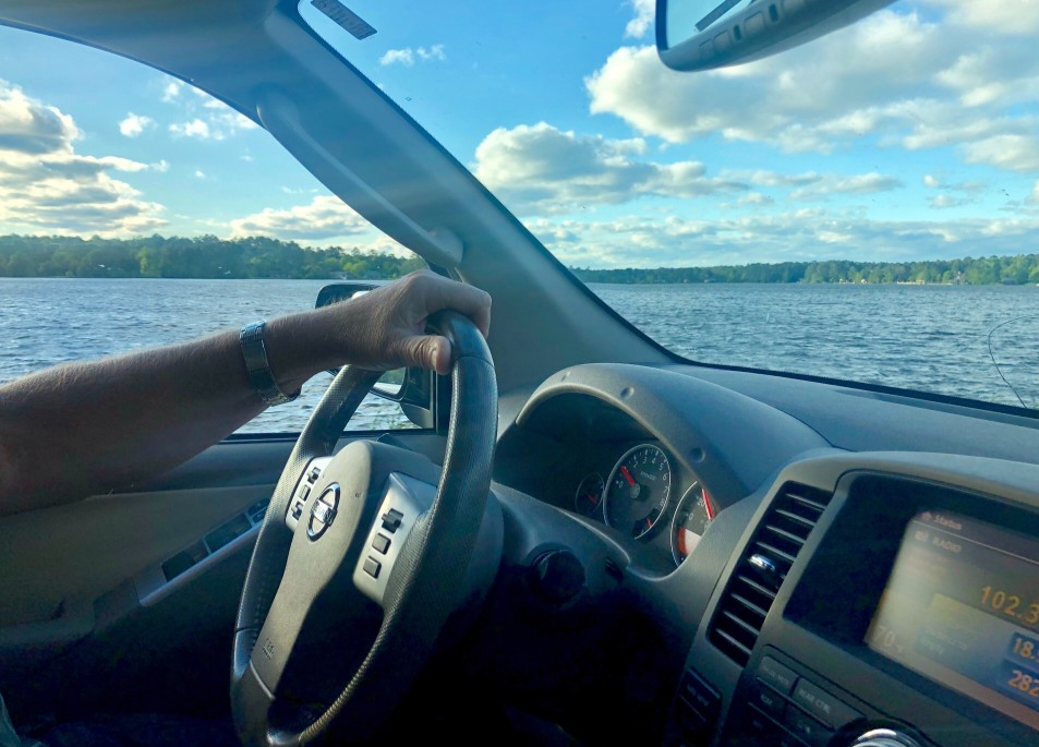 Person driving alongside lake living on the water