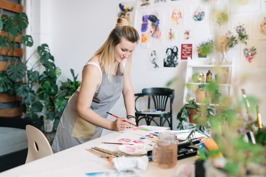 woman painting in art production studio