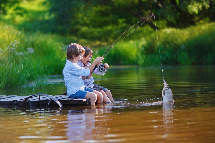 two little boys fishing in lake