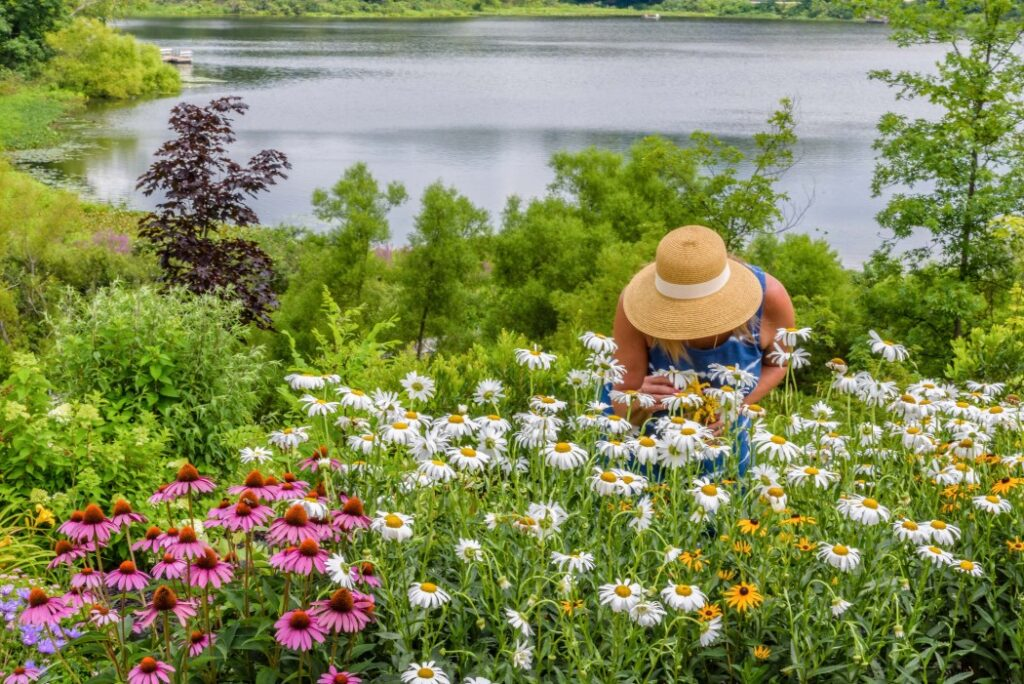 Woman smelling the flowers in her lake house cottage garden